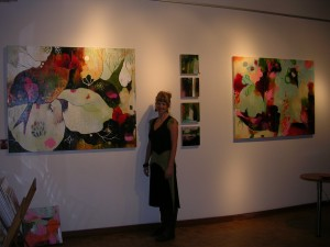 Flora S. Bowley beside her paintings at Artforte Gallery in Seattle's Pioneer Square